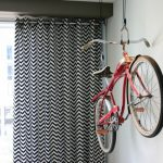 bike rack for apartment hanging rack curtain chevron patterns light colored wall window living room