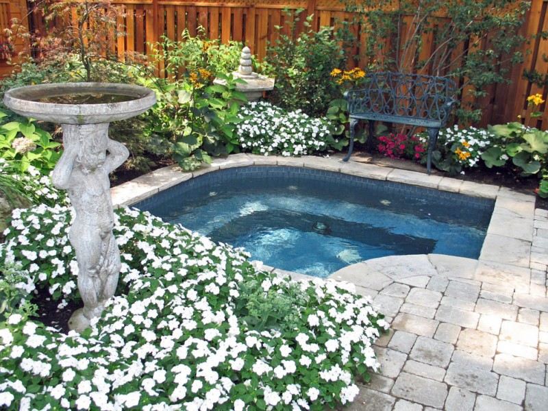 built in ground hot tob in white stones, surround by wood fence