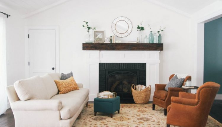 cedar mantle brick fireplace sofa carpet chairs small table bottles white pillows door window ceiling