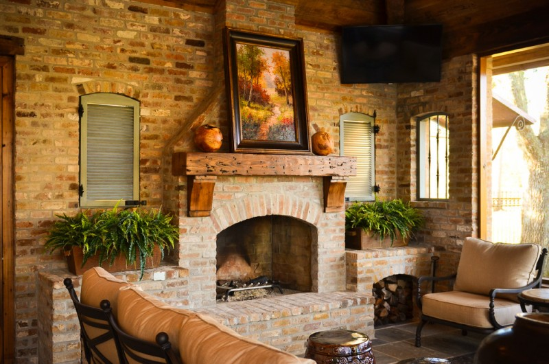 cedar mantle brick fireplace sofa small table windows plant wood painting bricks chair wall tv rustic style