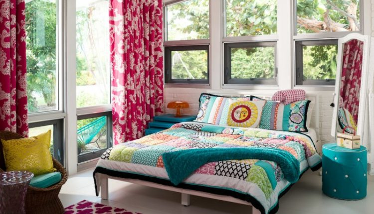 colorful bed sheet in mid century bedroom white bed turquoise bedside table turquoise side table white painted bricks walls area rug full length red curtains with motifs