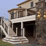 Composite Deck Idea With Huge Stone Pillar Exterior Staircase With Lightings Deep Brown Railing System And Light Beige Siding Exterior
