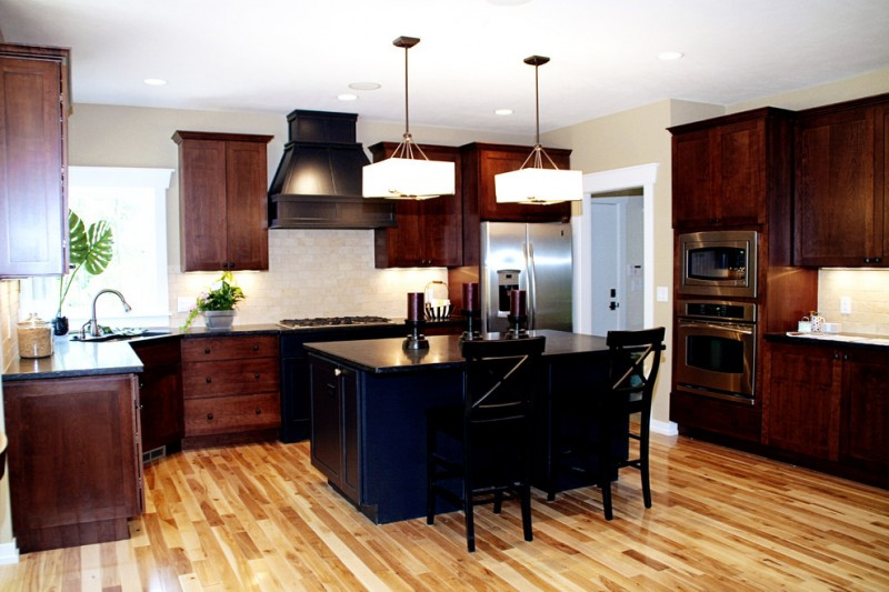 contemporary kitchenwith dark brown cabinet, black islan, white stonebacksplash, wood floor, white pendant lamps