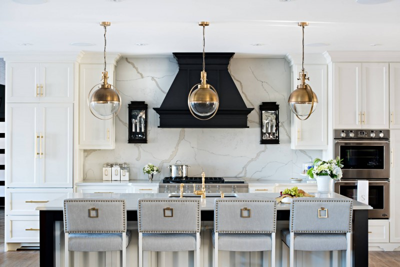 contemporary white cabinet golden glass pendant lights marble backsplash marble counter top dark hood grey bar stools