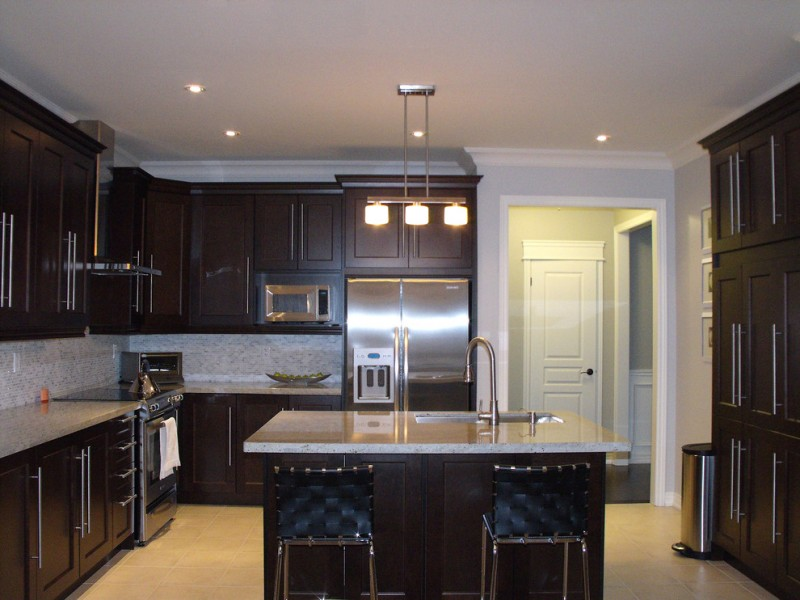 contemporary with dark cabinet, dark island with white counter top, white pendant, blue navy chair
