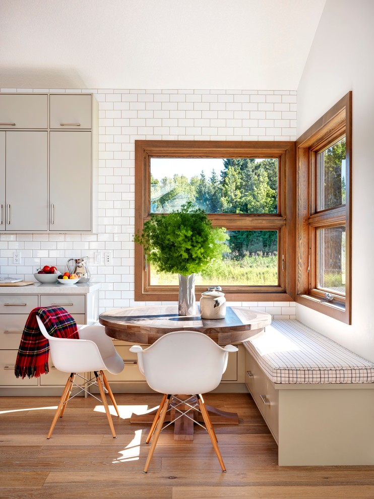 corner dining room with creamy bench with soft plaid cushion, white chairs, wooden table, near the window