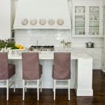 Country L Shaped Kitchen With White Marble Countertop White Subway Tile Backsplash White Marble Island With Purple Linen Covered Stools Shaker Cabinets White Cabinetry Dark Wood Floors