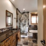 Craftsman Bathroom With All Kinds Of Brown Tiles In Floor, Wall In Shower Area, Half Walls In Bathtub Area, A Little In Dark Brown Counter Top Area, Dark Brown Cabinet, Mirror