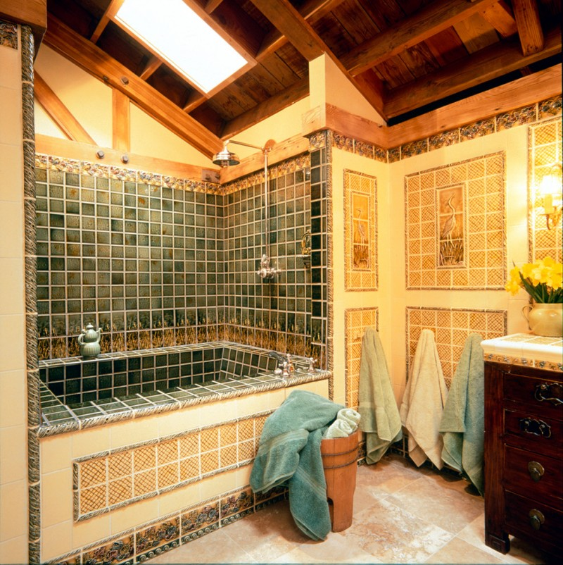 craftsman bathroom with bathtub in green tiles inside, green tiles in walls, orange tiles outside the tub, orange brown flooring, orange tiles walls outside the tub, dark brown cabinet
