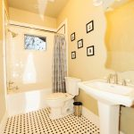 Craftsman Bathroom With Soft Orange Wall, White Wastafel, Mirror, White Toilet, Soft Orange Black Tiles, White Tub, White Tiles For Shower And Tub Area, Yellow Lighting
