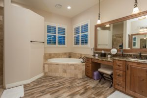 custom farm bathroom design granite top vanity with wooden cabinets stool large mirror with wood frames beige washed tiles floors terracotta bathtub's walls light beige bathroom walls