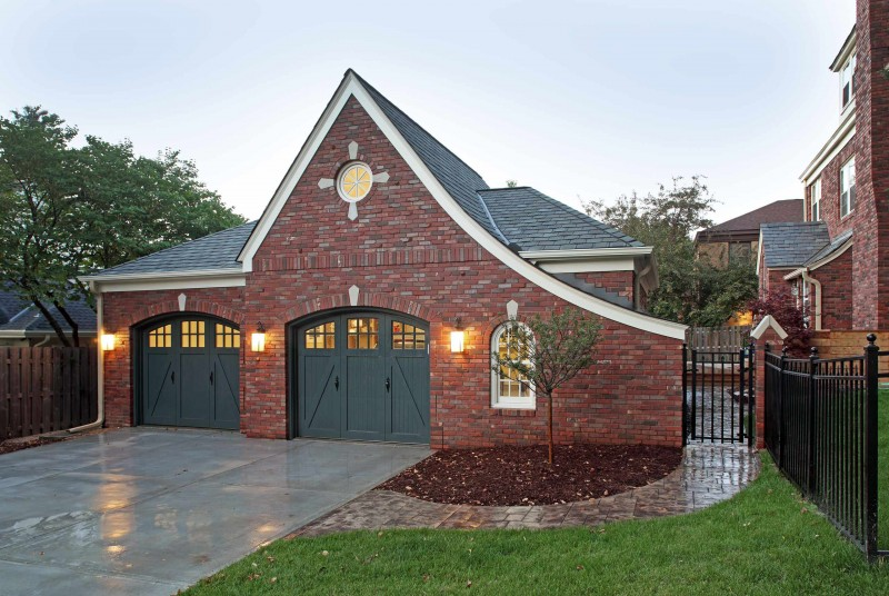 dark green garage wooden garage red brick wall stone walkway white window