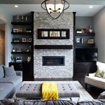 dark hardwood floor grey sofa modern pendant light brick fire place wall open floating shelves