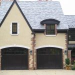 dark two car garage grey tiled roof beige siding brick siding