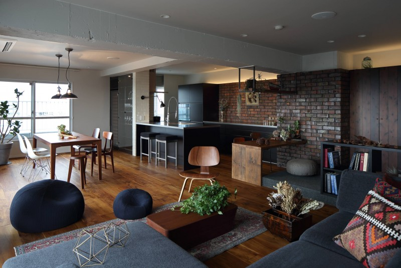 dark wood floor wooden table wooden stools contemporary black couches brick wall