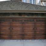 Dark Wooden Garage Arched Garage Door Stone Siding Grey Roof