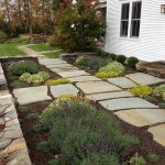 design footpath made by stone flowers garden soil white wall window door trees stones house exterior