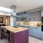 Eclectic Kitchen Idea With Purple Kitchen Island With Wood Top A Pair Of Dark Wood Stools Grey Cabinets Multicolored Backsplash Wood Countertop White Sink Stainless Steel Appliances