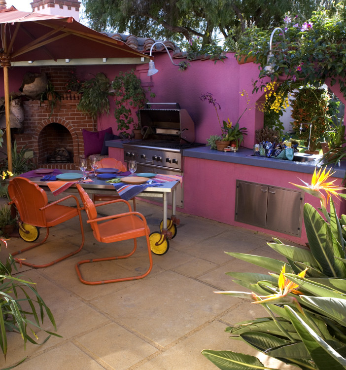 eclectic outdoor kitchen design with bold purple walls outdoor fireplace stainless steel BBQ stove dark grey countertop stainless steel movable table bright orange chairs beige floors