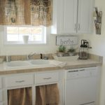 Farmhouse Kitchen Design With Unique Half Way Window Curtains Made Of Burlap Feed Sack Material Double Undermount Sinks In White White Cabinetry Light Brown Tiles For Backsplash
