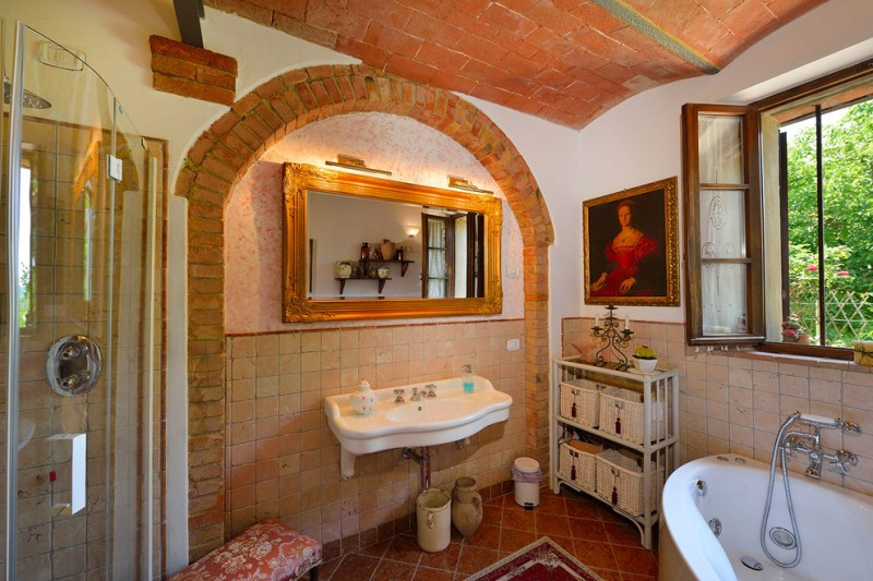 farmhouse mediterranean bathroom light terracotta walls dark terracotta floors wall mount sink in white corner white bathtub mirror with handcrafted wood frames walk in shower with glass panel doors
