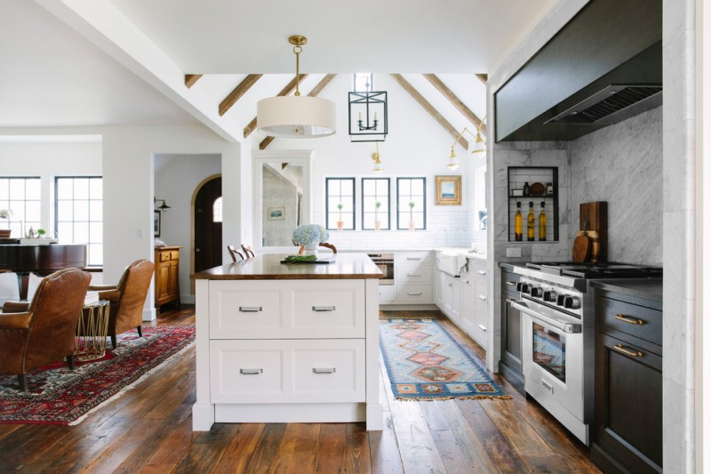 farmhouse open kitchen with cathedral ceiling in the itchen, white cabinet, darker cabinet for the cooker, wooden flooring until the living room