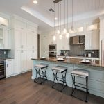 Floor To Ceiling White Cabinet Pendant Lights Marble Counter Top Wooden Floor Brick Backsplash Bar Stools