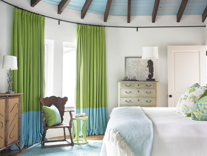 floor to ceiling window curtains in green blue colors black wrought iron curtain rods mounted on ceiling white bed linen andd blue comforter light blue rug woden chair small green side table