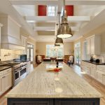 Granite Countertop White Cabinet Black Countertop Tiled Backsplash Golden Pendant Lights Stainless Steel Appliances