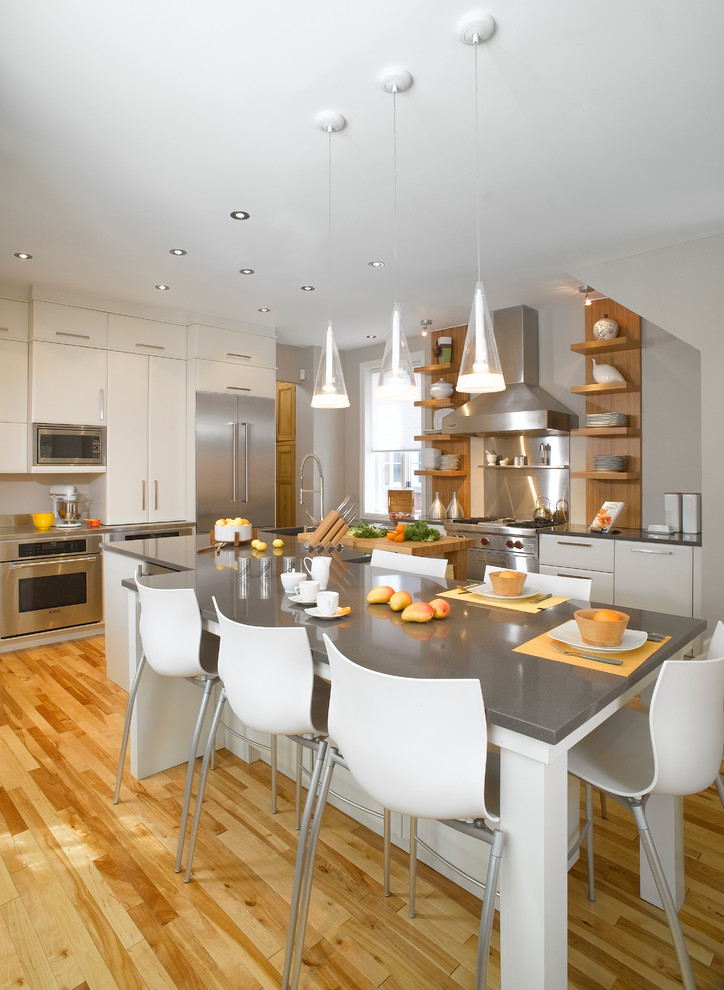 grey quartz countertop white kitchen wood floor dining chairs white glossy cabinets hanging lights shelves window