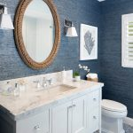 half bath with blue walls, wood framed mirror, white sonces, white cabinet with white countertop, white toilet, blue white tile flooring