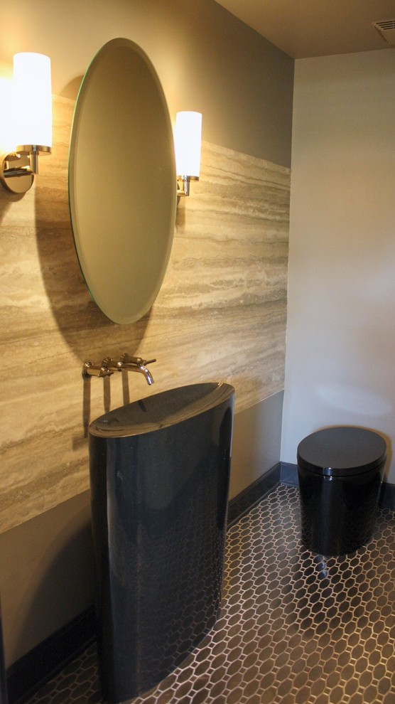 half bathroom with brown stony marble wall in one side with mirror, yellow sconces, black polished toilet, tall cylinder black sink