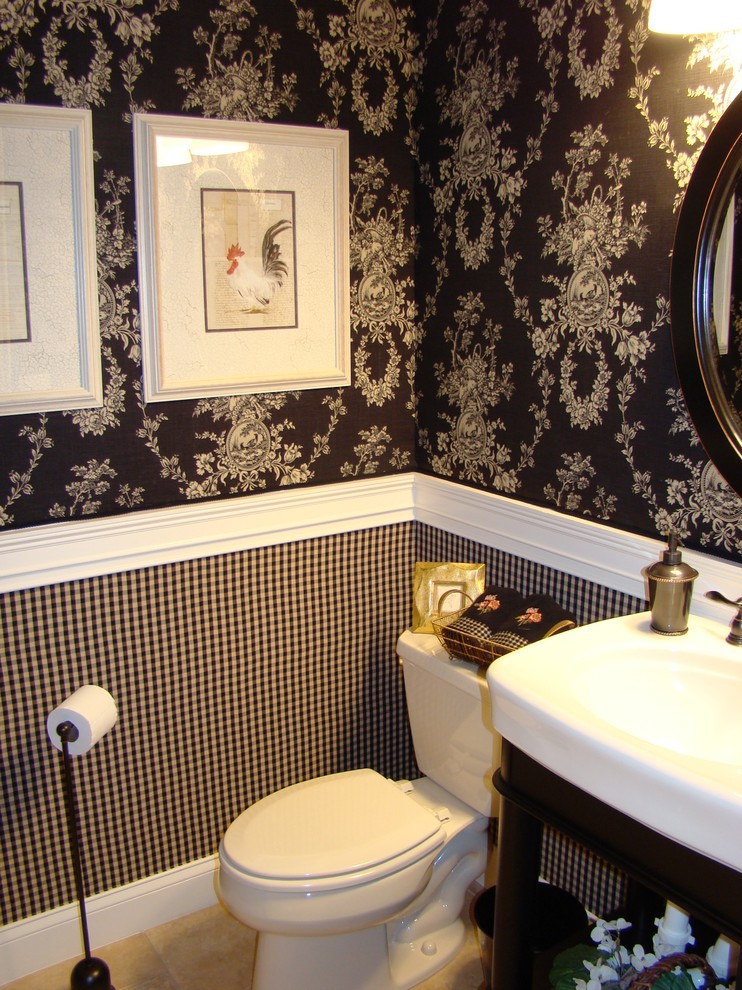 half bathroom with white toilet, white wink with wooden holder, black and white tile half bottom wall, white molding, black wallpaper with white flower