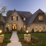 hill country house plans classic style windows stone walls exterior lamps grass flowers door oval window