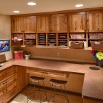 home office with brown wooden wall mounted cabinets and shelves on top of the table, and cabinets on the side