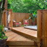 hot tub in three level decking from wood, surrounded by wood fence
