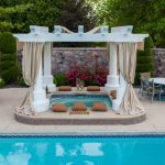 hot tub near the pool with white pergola with curtain