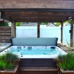 hot tub with with ipe decking, concrete counter, cedar pergola, tempered glass panels and firepit