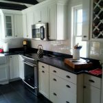 kitchen with black counter top white cabinet