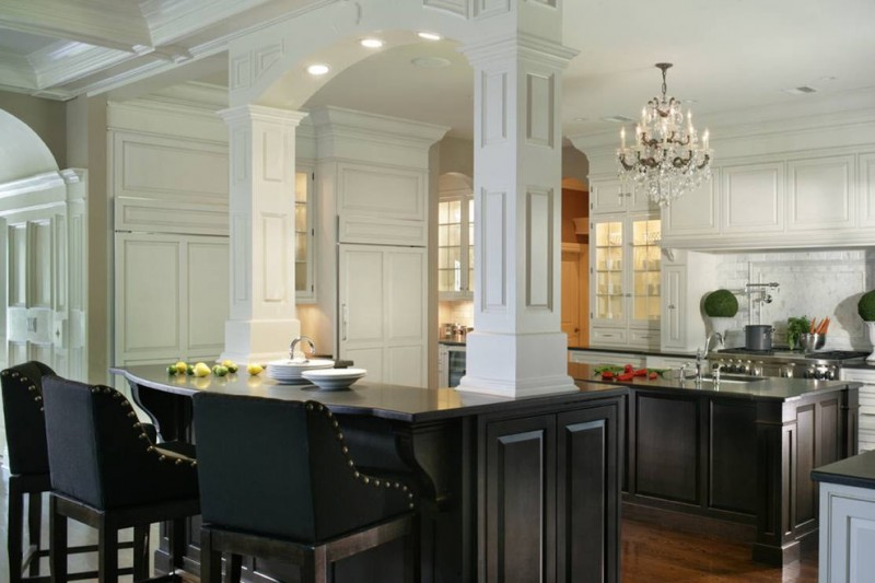 kitchen with white top cabinet, white wall, big white posts, black countertop, black kitchen island, black chair