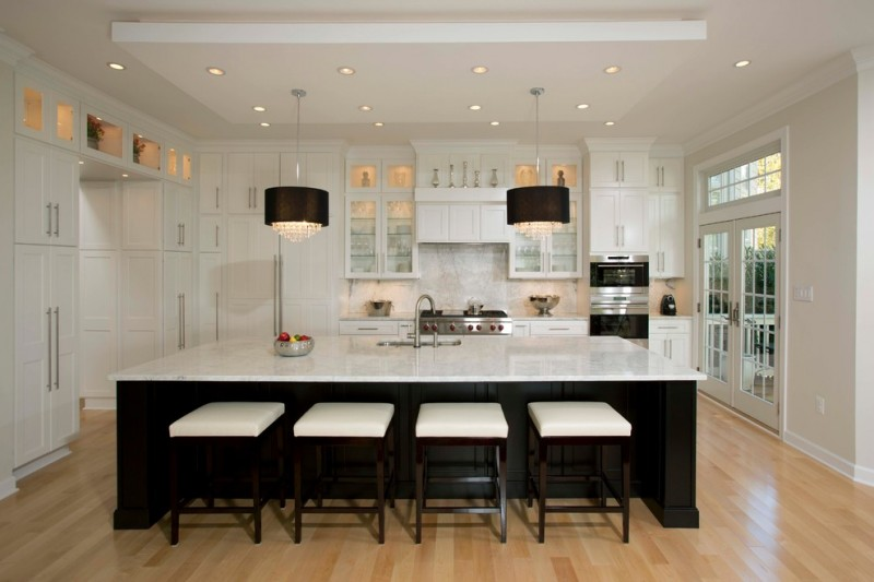 kitchen with white wall, door pane, countertop, cabinet, black kitchen islands, chairs with white cushion adn black legs