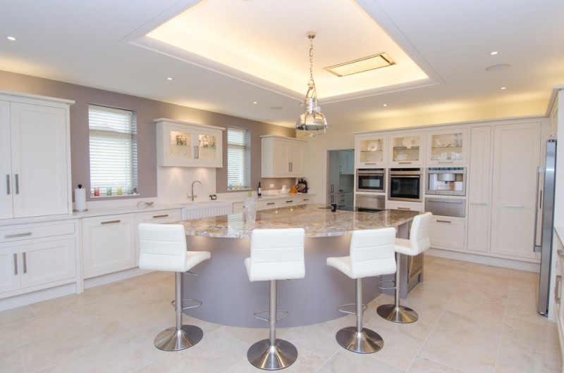 large kitchen remodel with light lavender breakfast bar modern white bar stools white shaker cabinets white cabinetry farmhouse sink white countertop stainless steel appliances