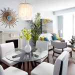 livign room in condo with wood flooring, white chair set with glass table, grey chairs, white sofa, glass coffee table, white fireplace, white wall, crystal chandelier