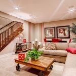 Living Room Basement With Beige Corner Sofa And Red Pillows, Wooden Coffee Table, Small Cabinet In The Corner