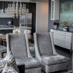 living room in a condo with grey chairs, grey cabinet, wood table grey walls, grey pendant, chandelier, grey sofa