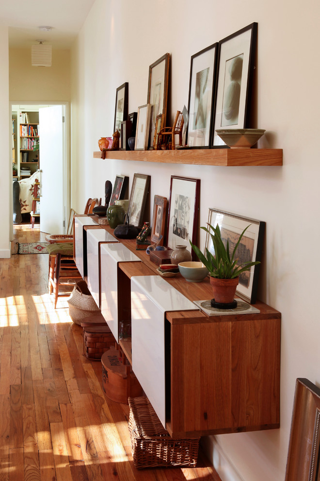 living room with brown wooden wall mounted cabinets and brown wooden wall mounted shelf