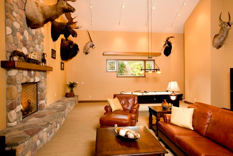 living room with warm brown wall, brown rug, brown leathered sofa, deer and bison wall mount, animals miniature