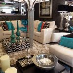 living room with white fur rug, white sofa, zebra pattern ottoman for table, zebra pattern pillow, chandelier