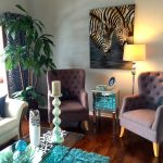 living room with white wall, wooden flooring, brown couches, white sofa, plants, zebra painting, blue fur ruf, glass coffee table