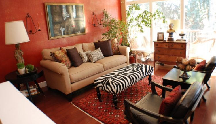 living room with zebra pattern ottoman as table, brown sofa, dark brown leathered couches, dark wood side table, white table lamp